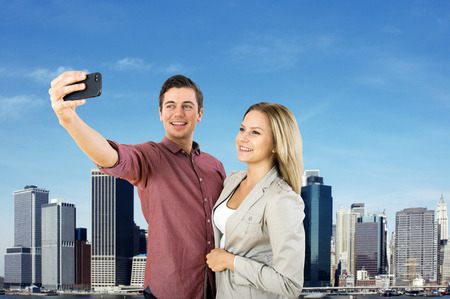 generation y: Young urban couple taking a selfie in front of the New York City Skyline