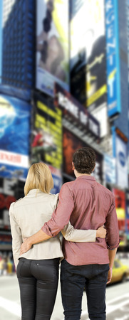 jetset: Young couple in a big city, looking at overwhelming billboards, screaming their product and marketing advertisements.