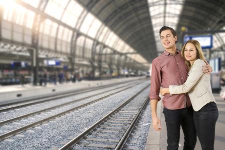 estacion de tren: Joven pareja abrazándose unos a otros en una estación de tren, a la espera de un tren para llegar, listo para ir a lugares.