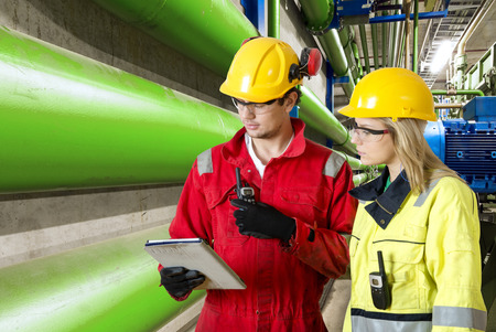 industrial industry: two maintenance engineers going through a checklist during a routine inspection of an industrial installation in a factory