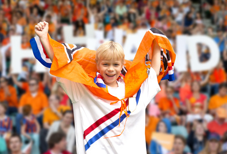 rooting: Young, ecstatic, supporter of the Dutch national team, rooting for the players in a crowded stadium, with many spectators in the background