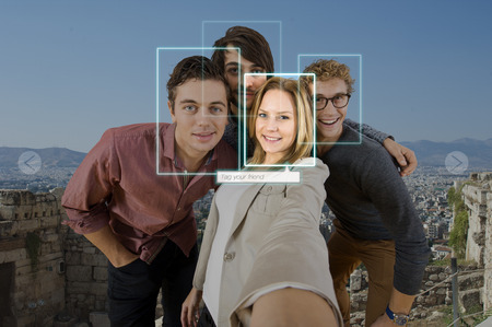 Tagging and sharing a friend in a selfie of four people using facial recogintion software applications in front of a large city for sharing on varous social media platforms Archivio Fotografico