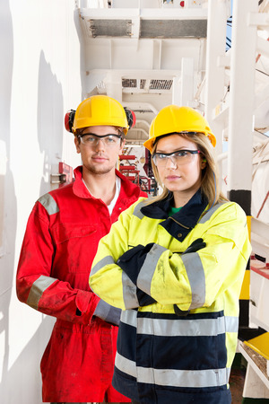 Two ship mates and crew members posing in he ang way on deck of an industrial supply vessel