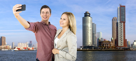 maas: Young couple taking a selfie in front of the tall high rise buildings in Rotterdam, on the banks of the river Meuse