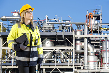 supervisores: Mujer, posando con una radio tableta y cb delante de una instalación petroquímica como oficial de planta y seguridad