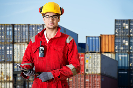 harbour: Logistics manager at a container transhipment plant, with an electronic tablet, and cb radio observing safety regulations Stock Photo