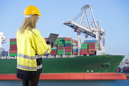 docker: Female docker overlooking the unloading of a large container ship in an industrial harbor, carrying an electronic consignment note on her tablet Stock Photo