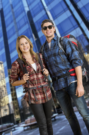 shoestring: Two backpackers, traveling on a shoestring, posing in front of a tall, glass, skyscraper,