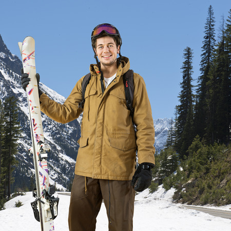 Smiling skier, wearing a helmet and goggles, with his skis in his hand posing on a beautiful day in a mountain landscape photo