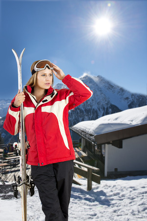 wintersports: young, pretty woman posing with her skis in front of a hill top restaurant in a ski resort