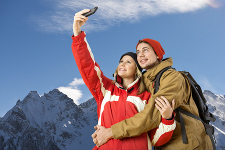 wintersports: young couple taking a selfie during wintersports of a magnificent view over an alpine mountain rainge