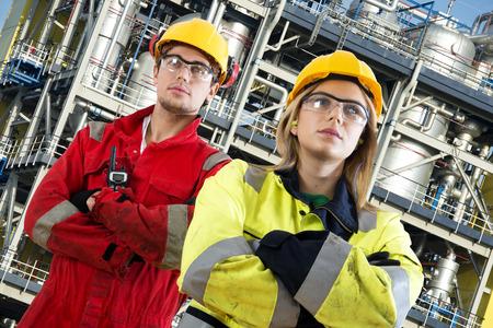 petrochemistry: Dos ingenieros de seguridad en sus puestos de trabajo, posando con confianza delante de una instalaci�n qu�mica grande con tanques, v�lvulas, tubos y estructuras de seguridad