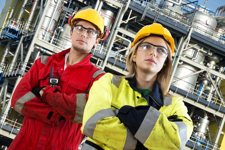technologists: Two security engineers at their jobs, posing confidently in front of a large chemical installation with tanks, valves, tubes and safety structures