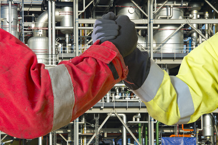 Hands of two engineers joining in closing a deal for the oil, gas and energy market as contractors, conceeding in a grant to cooperate on a joint venture. Foto de archivo