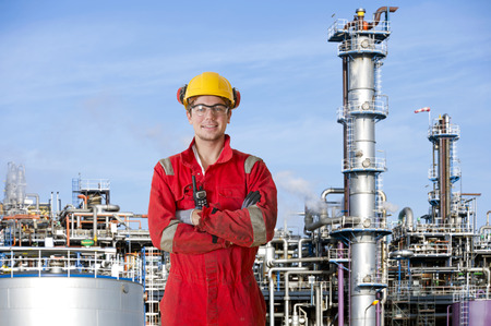 petrochemistry: Smiling man with his arms crossed, posing in front of a large petrochemical refinery
