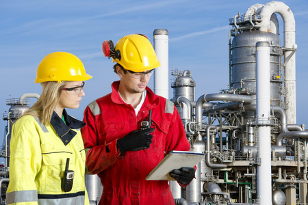 chimneys: Two engineers going through routine checks, working at a petrochemical oil refinery using cb radios and a tablet computer