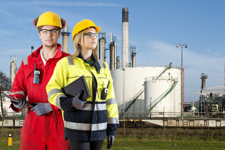 perimeter: Two safety specialists monitoring the perimeter of a petrochemical refinary, using electroncial devices, such as cb radios and tablets