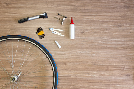 spoked: Background with bicycle tools laid out on a wooden floor, with a spoked wheel, tire levers, a pump, glue and a chain punch. Items, used to repair a flat tire