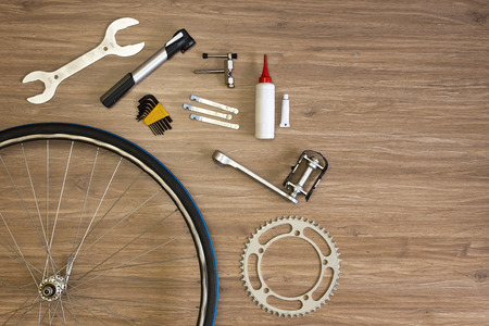 Assorted items, related with bicycle repair on a wooden background