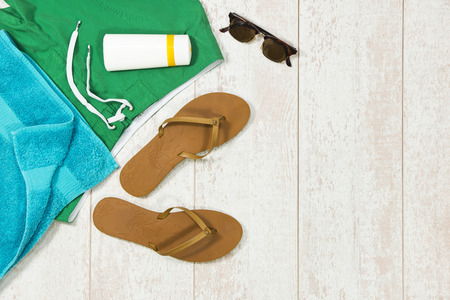 sun screen: Colorful background image with basic summer vacation items, such as swimming shorts, a towel, sunglasses, sun block and flip flop slippers