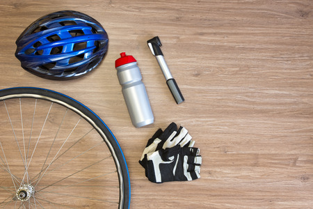 Cycling sports items arranged on a wooden background, seen from above. Items include a sports helmet, spoked wheel, drinking bottle, lightweight air pump and gloves Archivio Fotografico