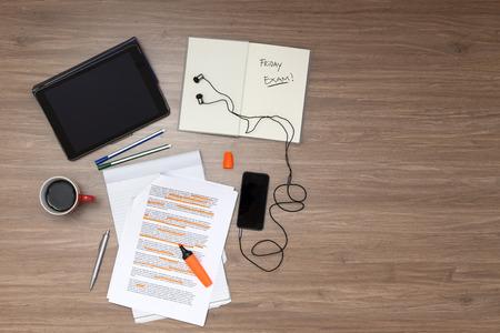 Achtergrond, gevuld met het bestuderen van materialen en kopieer ruimte op een houten ondergrond. Items zijn onder andere een elektronische tablet, muziekspeler, tekst boek, kop koffie, pennen, stiften, een hoge verlichte standaard (Lorum ipsum) tekst, van bovenaf gezien