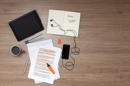 Background, filled with studying materials and copy space on a wooden surface. Items include an electronic tablet, music player, text book, cup of coffee, pens, markers, a high lighted standard (lorum ipsum) text, seen from above Foto de archivo