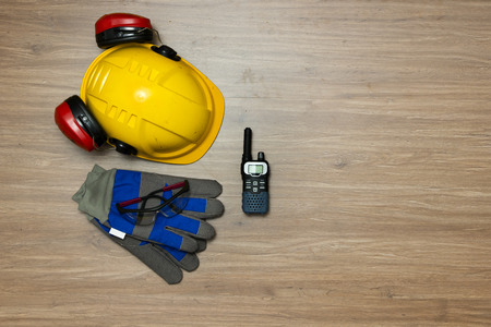 cb: Background of personal safety accessories on a wooden surface. Items include a hard hat with ear protection attached, safety goggles, working gloves and a cb radio Stock Photo
