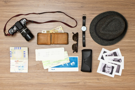 tickets: International travel background with a retro or vintage touch. Items include an old photo camera, passport, wallet with foreign currency, airplane ticket, hat, sunglasses and a couple of black and white photos Stock Photo