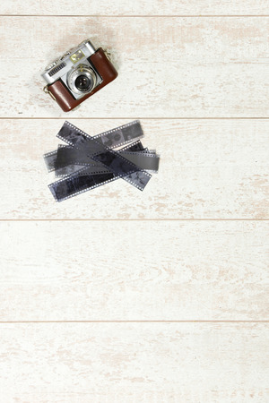 rangefinder: Vintage photography background with a retro rangefinder and 35 negative film strips on a white wooden surface