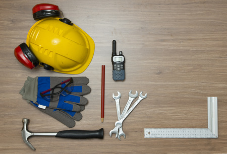 cb: Background with various personal safety accessories and assorted tools on a wooden surface. Items include a hard hat with ear protection attached, safety goggles, working gloves and a cb radio