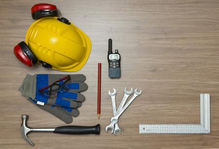 elementos de protección personal: Fondo con diversos accesorios de seguridad personal y variedad de herramientas sobre una superficie de madera. Los artículos incluyen un casco con protección para los oídos adjunto, gafas de seguridad, guantes de trabajo y una radio cb Foto de archivo