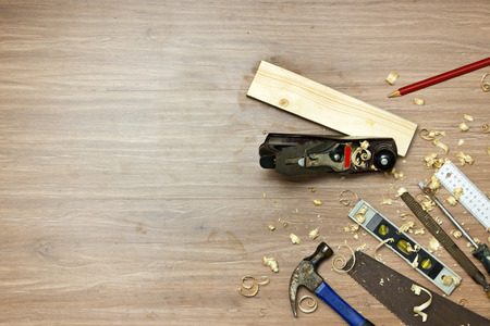 carpentry: Wood working tools, used in carpentry by a carpenter background. Assorted items, such as a hammer, a wood saw, a spirit level, grater, rasp, screw driver, a carpenters square and pencil, surrounded by wood shavings.