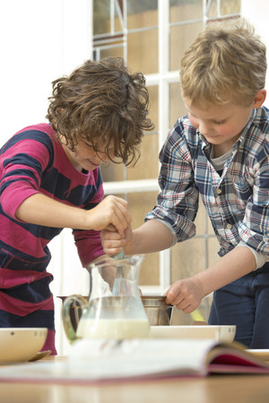 kids birthday party: Two kids whisking batter in a bowl during a baking workshop at home at a birthday party.