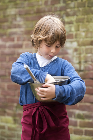 overs: Boy with a sweet tooth, muncing the left overs from batter  in a bowl hes holding