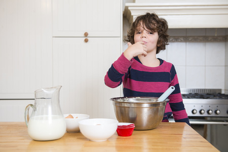 finger licking: Portrait of young girl licking batter while preparing cupcake in kitchen