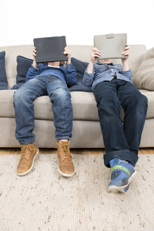 arcade games: Two boys, slouching on a couch in a living room, each plaing games on a tablet computer.