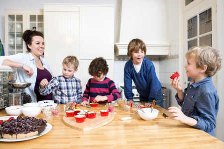 host: Boys and girls decorating cupcakes at a kitchen counter during a baking workshop for kids at a birthday party