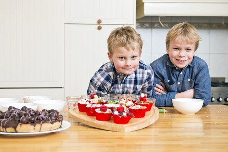 workship: Two brothers posing in a kitchen, together in front of a heart shaped cutting board with freshly baked and decorated cupcakes