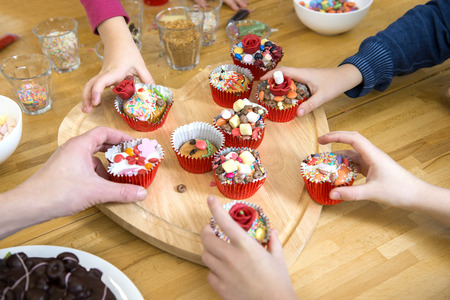 kids birthday party: Kids picking their favourite decorated cupcake from a heart shaped cutting board at a birthday party