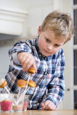 self indulgence: Boy putting cupcake pop in glass at kitchen counter