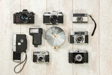 slr cameras: Directly above shot of various vintage cameras with flash on floorboard