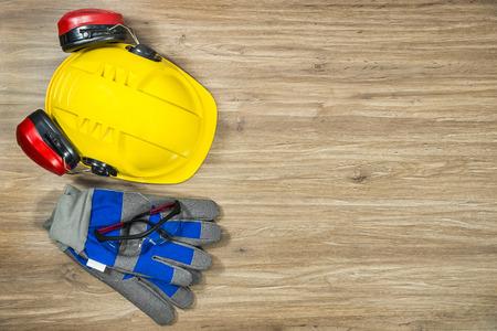 elementos de protección personal: Antecedentes de accesorios de seguridad personal en una superficie de madera. Los artículos incluyen un casco con protección para los oídos adjunto, gafas de seguridad y guantes de trabajo