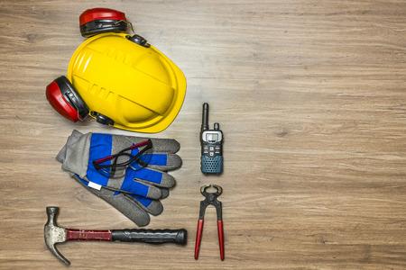 elementos de protección personal: Antecedentes de accesorios de seguridad personal en una superficie de madera. Los artículos incluyen un casco con protección para los oídos adjunto, gafas de seguridad, guantes de trabajo, un martillo, tenazas y una radio cb