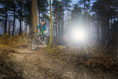 mountain biker: Mountain biker riding his bike on a gravel dirt trail, with the sun in his back at dusk