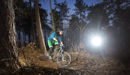 mountain biker: Mountain biker cycling through the woods on an off road trail at sunset. Backlit image