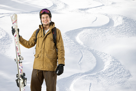 off piste: Young off piste skier standing in front of fresh tracks in the powder snow with skis in his hand Stock Photo