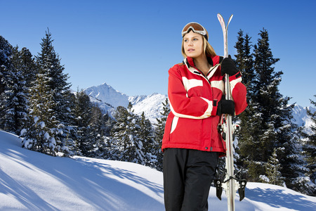 wintersports: Pretty young women, holding her skies in front of an alpine mountain range with snow covered trees and fresh powder snow, Stock Photo