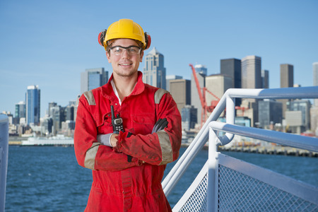cb: Docker and deck hand posing on the bridge of a ship, about to moor off in a city harbor, with the seattle skyline in the background Stock Photo