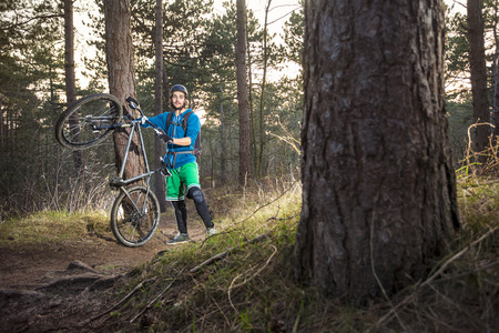 mountainbike: Mountain biker cycling standing by an off road trail through the woods in the late afternoon Stock Photo